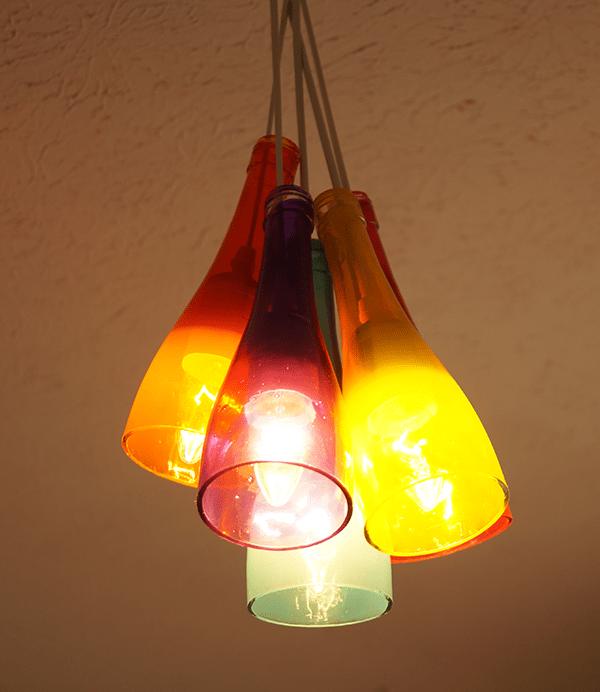 Un lampadario colorato fatto con bottiglie di vetro